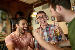 Football fans or friends with beer at sport bar. People, leisure, friendship and entertainment concept - happy football fans or male friends drinking beer and Stock Photography