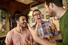 Football fans or friends with beer at sport bar. People, leisure, friendship and entertainment concept - happy football fans or male friends drinking beer and royalty free stock photos