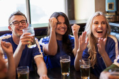 Football fans or friends with beer at sport bar. Sport, people, leisure, friendship and entertainment concept - happy football fans or friends with beer watching stock images