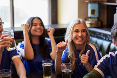 Football fans or friends with beer at sport bar. Sport, people, leisure, friendship and entertainment concept - happy football fans or friends with beer watching Stock Photography