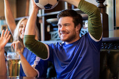 Football fans or friends with beer at sport bar. People, leisure, soccer and sport concept - happy football fans or friends with beer and ball celebrating Royalty Free Stock Images