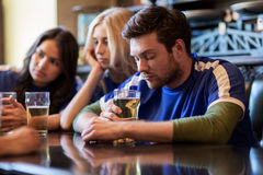 Football fans or friends with beer at sport bar. People, leisure, soccer and sport concept - unhappy football fans or friends with beer at bar or pub stock images