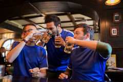 Football fans or friends drink beer at sport bar. Sport, people, leisure, friendship and entertainment concept - happy football fans or male friends drinking stock photo