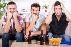 Football fans. Group of sports fans watching game on TV at home Stock Photography