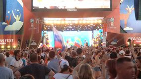 Football fans at the official FIFA FAN FEST zone. SAMARA - JUNE 25, 2018: Football fans dancing and waving hands and flags after the game Uruguay - Russia at the stock video footage