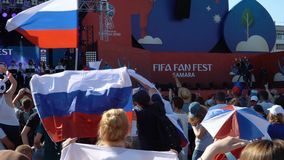 Football fans at the official FIFA FAN FEST zone. SAMARA - JUNE 25, 2018: Football fans waving hands and flags, dancing before the game Uruguay - Russia at the stock footage