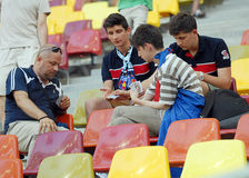 Football Fans playing cards in the stand Royalty Free Stock Photo