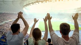 Football fans raising hands, chanting, supporting national team at stadium. Stock photo stock photos