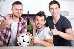 Football fans. Rear view of three excited soccer fans sitting on sofa and looking at the camera Stock Photography