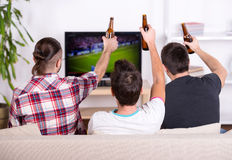 Football fans. Rear view of three excited soccer fans sitting on sofa and watching favorite team goal at tv Royalty Free Stock Photo