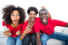 Football fans in red cheering on the sofa with beers Royalty Free Stock Image