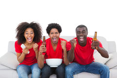 Football fans in red cheering on the sofa Royalty Free Stock Image