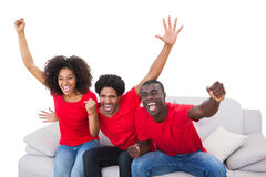 Football fans in red cheering on the sofa Royalty Free Stock Photography