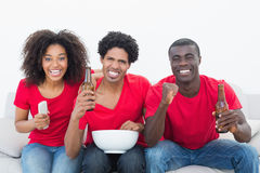 Football fans in red sitting on couch with beer and popcorn Stock Images