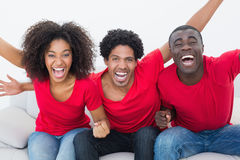 Football fans in red sitting on couch cheering Royalty Free Stock Photo