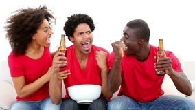 Football fans in red sitting on couch cheering stock footage