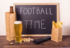 Football fans setting of beer bottle in brown paper bag, glass,. Chips, pistachio, tv remote control and handwriting text football time written in chalkboard royalty free stock photography
