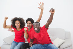 Football fans sitting on couch cheering together stock image