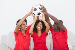 Football fans sitting on couch holding ball Stock Photography
