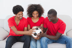 Football fans sitting on couch holding ball Royalty Free Stock Image