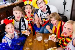 Football fans in sports bar watching a game with excitement. Wearing flags and make-up stock photo