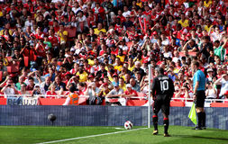Football fans at stadium. The Arsenal football fans watch Clarence Seedorf kicking a corner during the match Arsenal - A.C. Milan valid for the 2010 Emirates Cup royalty free stock images