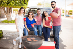 Football fans tailgating at a game and drinking. Group of good looking friends and football fands grilling hamburgers and drinking beer while tailgating at a stock photo