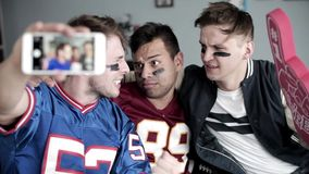 Football fans. Taking a selfie in home interior stock video footage