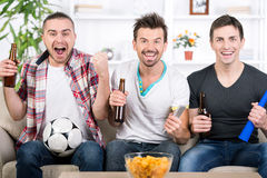 Football fans. Three football fans are cheering football match at home Royalty Free Stock Photography