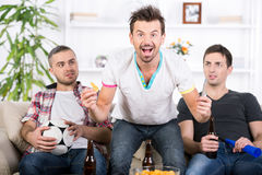 Football fans. Three football fans are cheering football match at home Stock Images