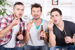 Football fans. Three football fans are watching game on TV at home with beer, pizza Royalty Free Stock Image