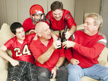 Football Fans Toast Success. Superbowl football fans toasting success with their beer bottles stock photo