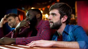 Football fans watching game in pub, male friends disappointed with team lose stock photo