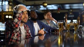 Football fans watching match in pub, frustrated with missed goal, losing game. Stock footage stock video