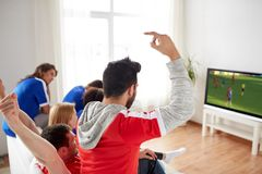 Football fans watching soccer game on tv at home. Sport, people and entertainment concept - happy friends or football fans watching soccer game on tv and Stock Image