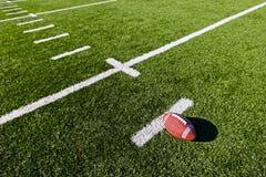 Football on Field. Football on Yardage Marker(s) shallow DOF Stock Photos