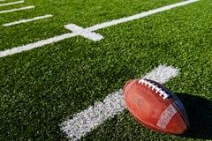 Football on Field. Football on Yardage Marker. Shallow DOF Stock Photo