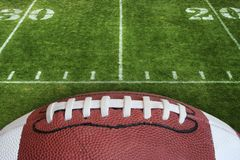 Football and field. A photo of an American Football with the focus on the leather texture and laces or threads with a football field in the background royalty free stock images
