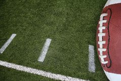 Football and field. A photo of an American Football field yardage markings with a football on the right border Stock Photos