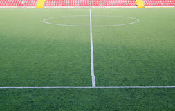 Football field. A green football field with red chairs Royalty Free Stock Image