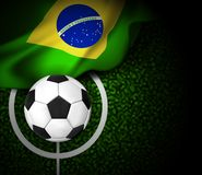Football field with ball and flag of Brazil Stock Photos