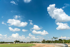 Football field and blue cloud sky. Royalty Free Stock Photo