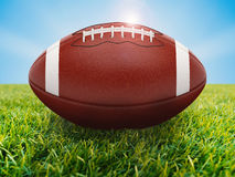 Football on field. 3d rendering american football ball on green field with blue sky Royalty Free Stock Image