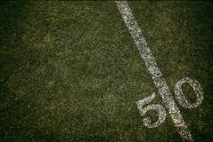 Football field ground fifty yard line. Friday night lights. Looking down from above stock photo