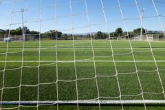 Football field in a sport complex. Soccer field through the goal net in a sports complex royalty free stock photography