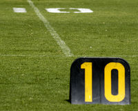 Football field ten yard line. Ten yard sign on a football field with the chalk number 10 in the background Royalty Free Stock Photos