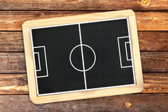 Football field on wooden wall. Football field on chalkboard with wooden frame on brown wooden wall stock photos