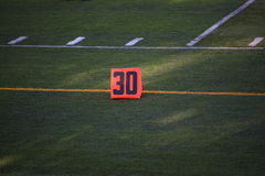 Football Field Yard Marker. Thirty yard line marker on grass turf playing field Stock Images