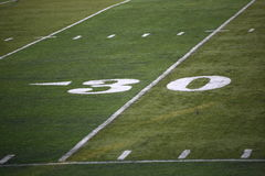 Football Field Yard Marker. Thirty yard line marker on grass turf playing field Stock Photos