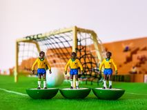 Football figures lined up on a grass field stock image